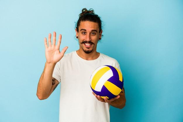 Giovane uomo caucasico con i capelli lunghi isolato su sfondo blu sorridente allegro che mostra il numero cinque con le dita.