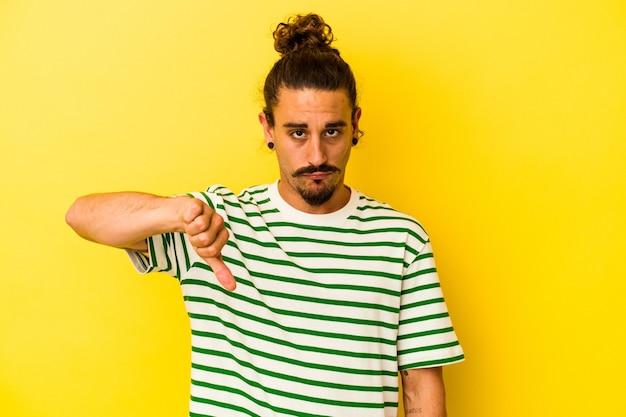 Giovane uomo caucasico con i capelli lunghi isolato su sfondo giallo che mostra un gesto di antipatia, pollice in giù. concetto di disaccordo.