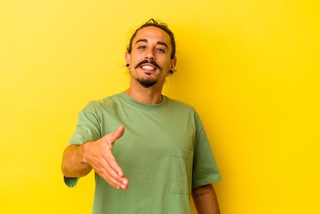 Giovane uomo caucasico con i capelli lunghi isolato su sfondo giallo che allunga la mano alla telecamera in gesto di saluto.