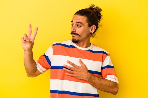 Giovane uomo caucasico con i capelli lunghi isolato su sfondo giallo prestando giuramento, mettendo la mano sul petto.