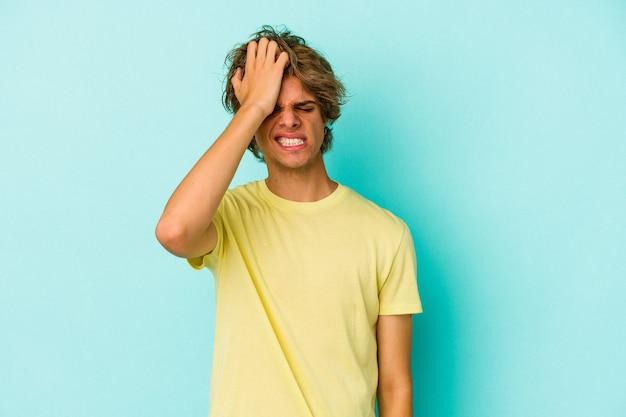 Giovane uomo caucasico con trucco isolato su sfondo blu, dimenticando qualcosa, schiaffeggiando la fronte con il palmo e chiudendo gli occhi.