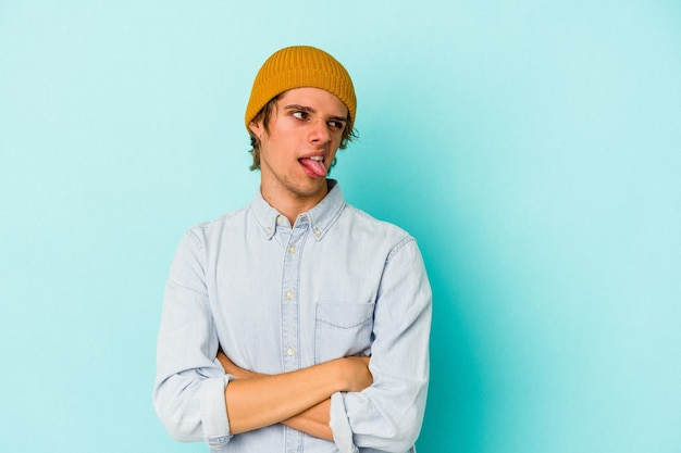 Giovane uomo caucasico con make up isolato su sfondo blu divertente e amichevole conficca fuori la lingua.