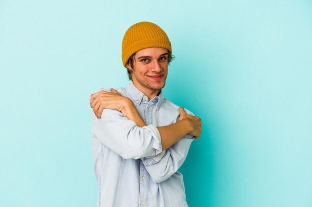 Giovane uomo caucasico con trucco isolato su sfondo blu abbracci, sorridendo spensierato e felice.
