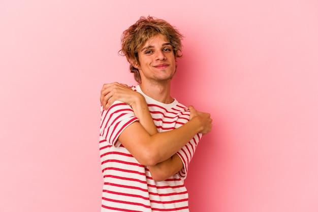 Giovane uomo caucasico con trucco isolato su sfondo rosa abbracci, sorridendo spensierato e felice.