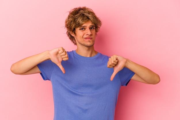 Giovane uomo caucasico con trucco isolato su sfondo rosa che mostra il pollice verso il basso, concetto di delusione.