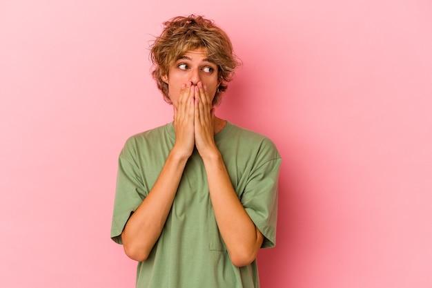 Giovane uomo caucasico con trucco isolato su sfondo rosa premuroso guardando uno spazio copia che copre la bocca con la mano.