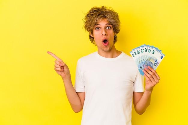 Giovane uomo caucasico con banconote in possesso di trucco isolate su sfondo giallo che puntano al lato
