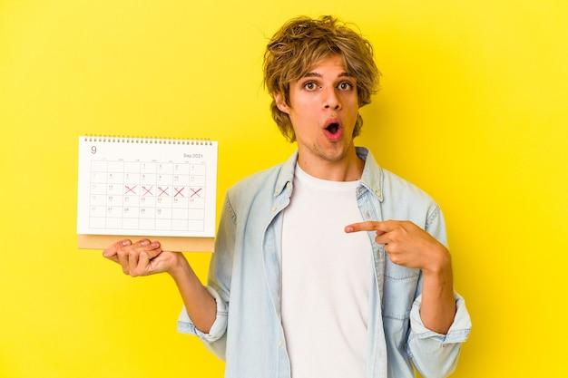 Giovane uomo caucasico con il calendario della tenuta del trucco isolato su sfondo giallo che punta al lato