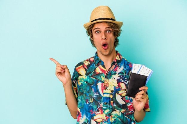 Giovane uomo caucasico con il trucco che tiene passaporto isolato su sfondo blu che punta al lato