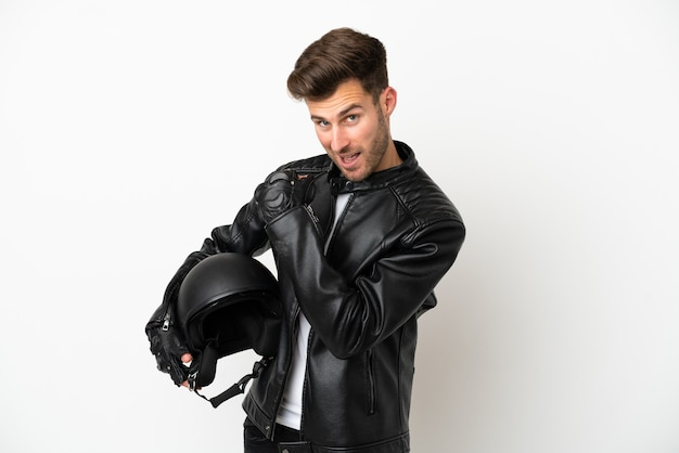 Giovane uomo caucasico con un casco da motociclista isolato su sfondo bianco che celebra una vittoria