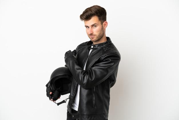 Giovane uomo caucasico con un casco da motociclista isolato su sfondo bianco che punta indietro