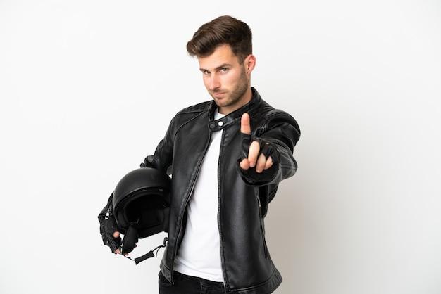 Giovane uomo caucasico con un casco da motociclista isolato su sfondo bianco che mostra e solleva un dito