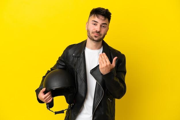 Giovane uomo caucasico con un casco da motociclista isolato su sfondo giallo che invita a venire con la mano. felice che tu sia venuto