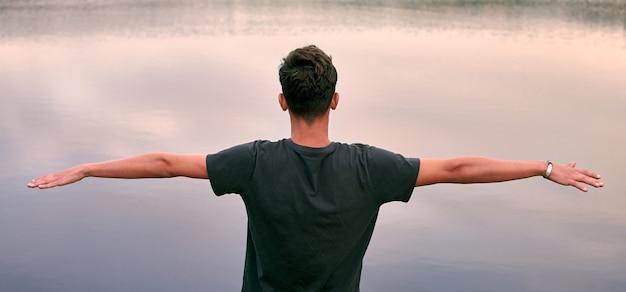 Un giovane uomo caucasico con le braccia aperte davanti a un lago che gode del panorama