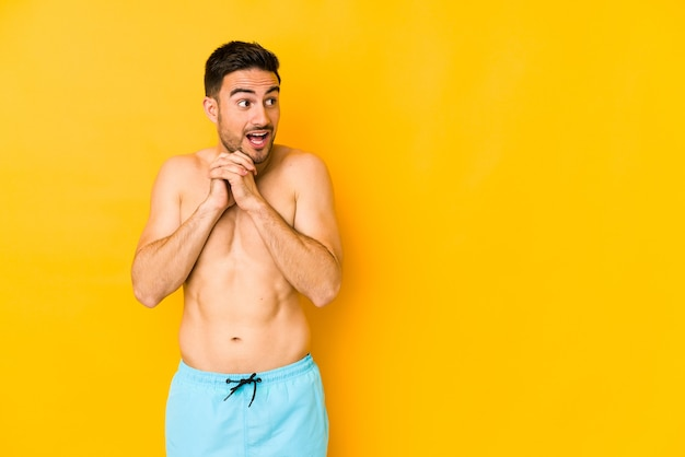 Giovane uomo caucasico con costume da bagno isolato su sfondo giallo giovane uomo caucasico con trpraying per fortuna, bocca stupita e apertura alla ricerca di fronte.
