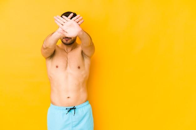 Giovane uomo caucasico con costume da bagno giovane uomo caucasico con due braccia incrociate trkeeping, concetto di negazione.