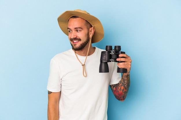 Il giovane uomo caucasico con i tatuaggi che tiene il binocolo isolato su fondo blu guarda da parte sorridente, allegro e piacevole.