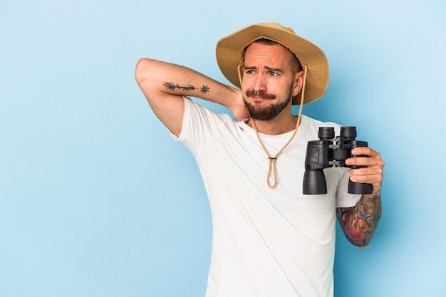 Giovane uomo caucasico con tatuaggi che tengono il binocolo isolato su sfondo blu toccando la parte posteriore della testa, pensando e facendo una scelta.