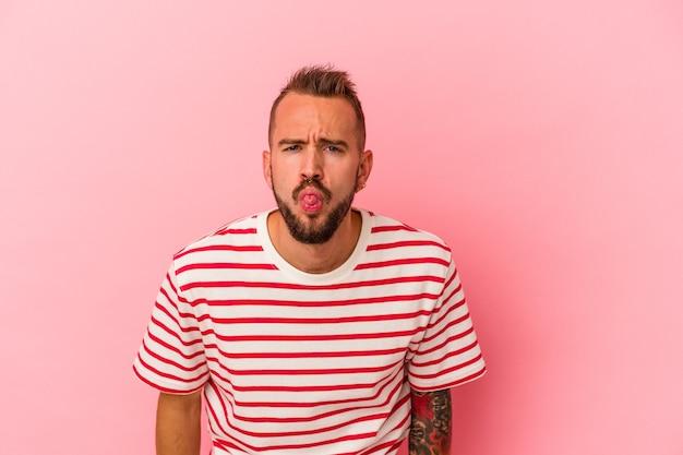 Giovane uomo caucasico con tatuaggi isolati su sfondo rosa divertente e amichevole con la lingua fuori.