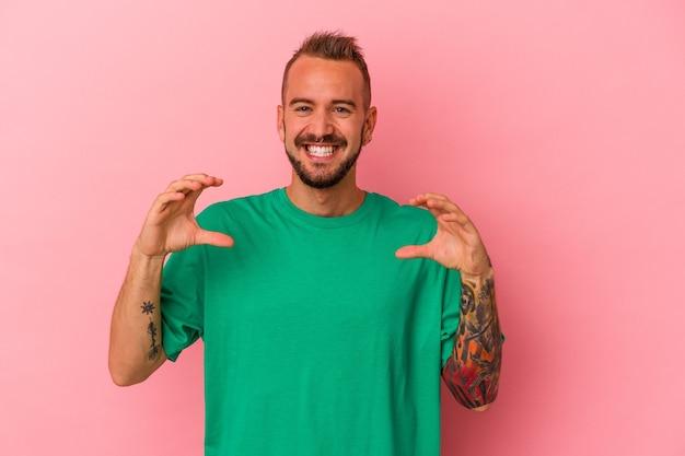 Giovane uomo caucasico con tatuaggi isolati su sfondo rosa che tiene qualcosa con le palme, offrendo alla telecamera.
