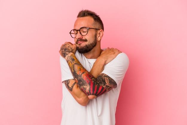 Il giovane uomo caucasico con i tatuaggi isolati sugli abbracci rosa del fondo, sorride spensierato e felice.
