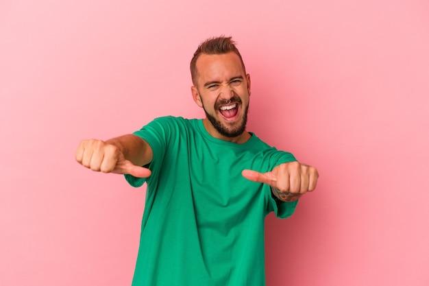 Giovane uomo caucasico con tatuaggi isolati su sfondo rosa alzando entrambi i pollici, sorridente e fiducioso.