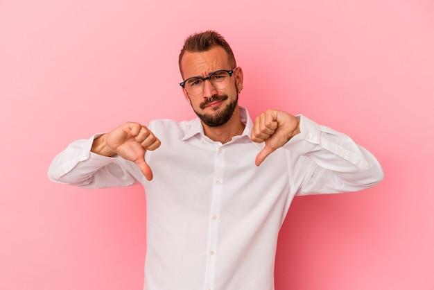Giovane uomo caucasico con tatuaggi isolati su sfondo rosa che mostra il pollice verso il basso, concetto di delusione.