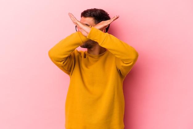 Giovane uomo caucasico con tatuaggi isolati su sfondo giallo mantenendo due braccia incrociate, concetto di negazione.
