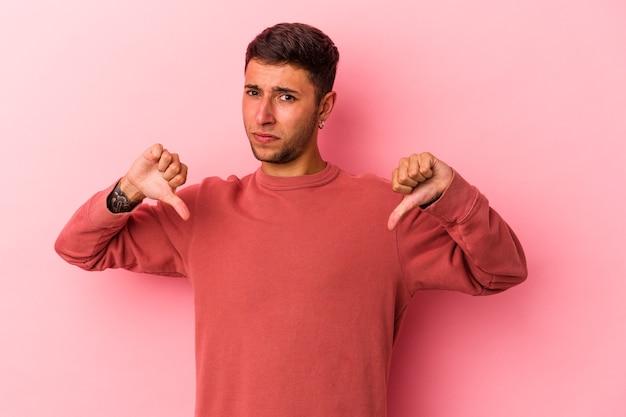 Giovane uomo caucasico con tatuaggi isolati su sfondo giallo che mostra il pollice verso il basso, concetto di delusione.