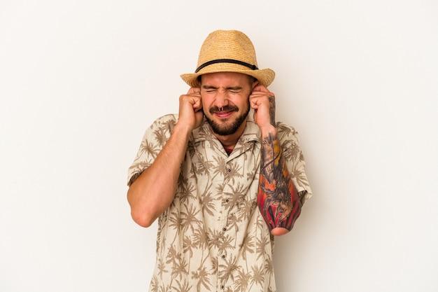 Giovane uomo caucasico con tatuaggi che indossa abiti estivi isolati su sfondo bianco che copre le orecchie con le mani.