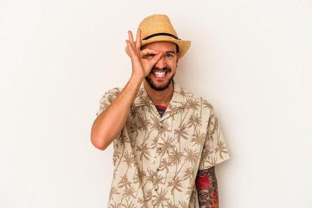 Giovane uomo caucasico con tatuaggi che indossa abiti estivi isolati su sfondo bianco eccitato mantenendo il gesto ok sull'occhio.