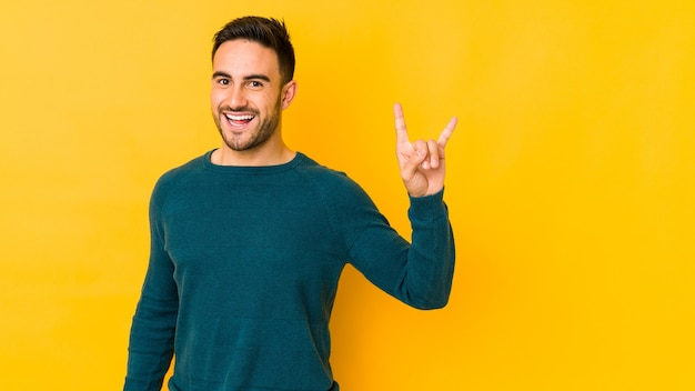Giovane uomo caucasico su bakground giallo che mostra un gesto di corna come un concetto di rivoluzione. Foto Premium