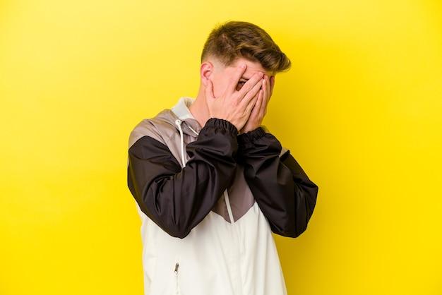 Giovane uomo caucasico su giallo lampeggia attraverso le dita spaventato e nervoso.