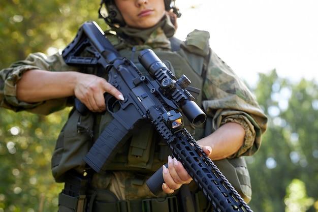 La giovane donna militare caucasica tiene una pistola in mano nella natura
