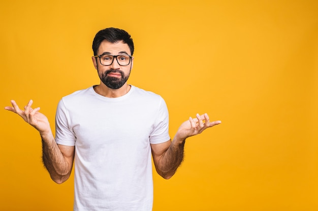 Giovane caucasico confuso confuso uomo barbuto diffondendo le mani oops gesto isolato su sfondo giallo