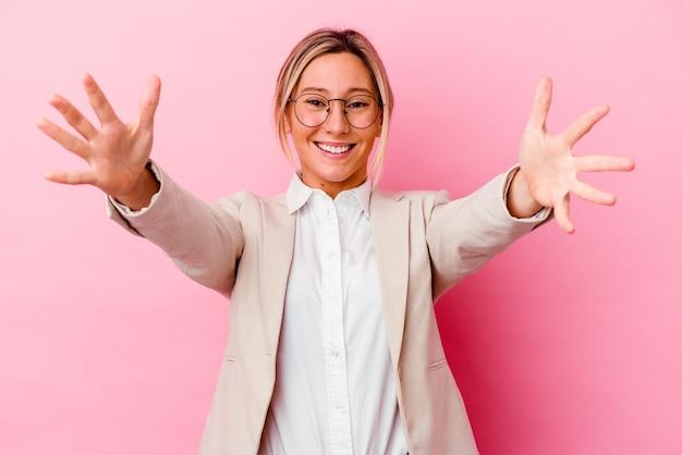 La giovane donna caucasica di affari della corsa mista isolata su fondo rosa si sente sicura di dare un abbraccio alla telecamera.