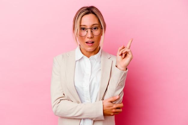 Giovane donna caucasica di affari di razza mista isolata su sfondo rosa con una grande idea, il concetto di creatività.