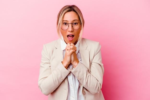 Giovane donna caucasica di affari della corsa mista isolata su fondo rosa che prega per fortuna, bocca stupita e di apertura che osserva alla parte anteriore.