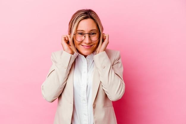 Giovane donna caucasica di affari della corsa mista isolata sulle orecchie rosa del rivestimento della parete con le mani.