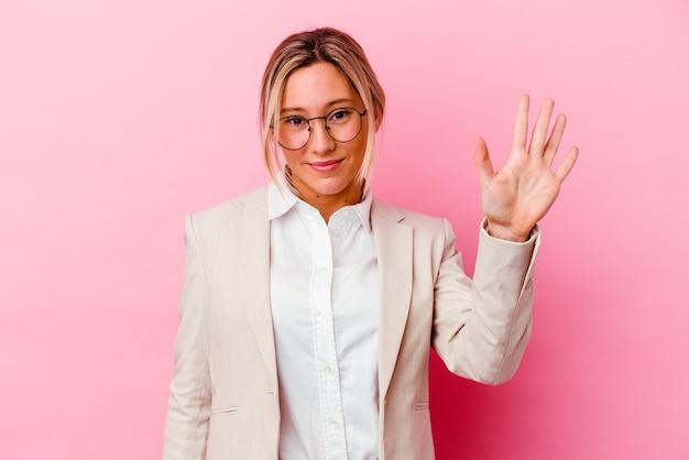 Giovane donna caucasica di affari di razza mista isolata sul muro rosa sorridente allegro che mostra il numero cinque con le dita.