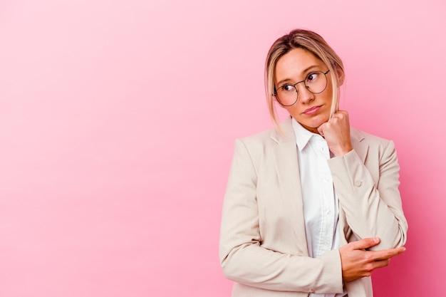 Giovane donna caucasica di affari di razza mista isolata sulla parete rosa che si sente triste e pensierosa, guardando lo spazio della copia.