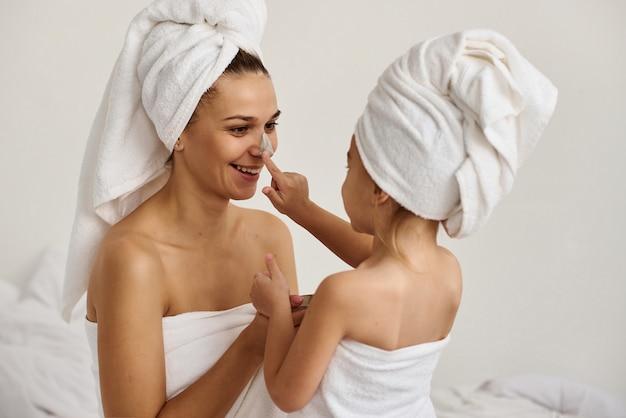 Giovane madre caucasica e figlia piccola con i capelli avvolti in teli da bagno bianchi applicano una maschera di argilla sui volti della madre