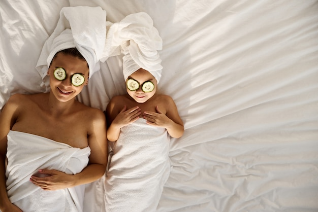 Giovane madre caucasica e figlia piccola con i capelli avvolti in teli da bagno bianchi distesi sul letto e applicare pezzi di cetriolo ai loro occhi. spa per famiglie. vista dall'alto
