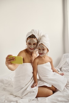 Giovane madre caucasica e figlia piccola con i capelli avvolti in teli da bagno bianchi con una maschera sul viso si divertono e fanno selfie al telefono
