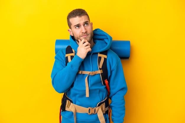 Uomo giovane alpinista caucasico con un grande zaino isolato