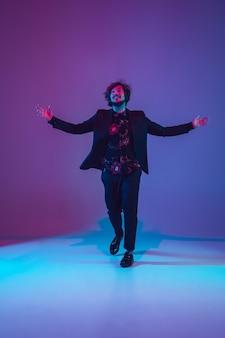 Giovane musicista caucasico in una danza casual su sfondo blu-viola sfumato alla luce al neon. concetto di musica, hobby, festival. ospite gioioso della festa, dj, stand in alto, ballerino. ritratto colorato dell'artista.