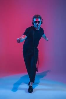 Giovane musicista caucasico che canta, balla alla luce al neon