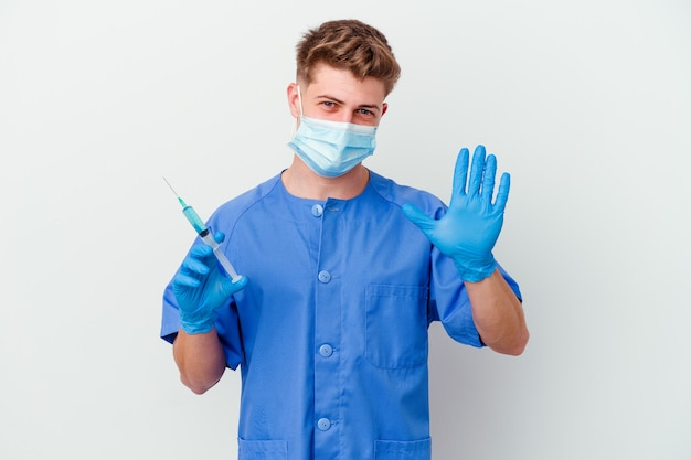 Il giovane uomo caucasico dell'infermiera ha preparato a dare un vaccino isolato sul muro bianco sorridente allegro che mostra il numero cinque con le dita