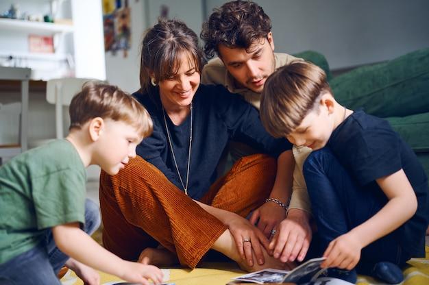 Giovani genitori caucasici che trascorrono del tempo a casa con i figli e leggono libri sul pavimento. famiglia felice che gioca con i bambini in età prescolare. concetto di educazione domestica