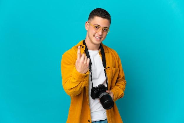 Giovane uomo caucasico del fotografo isolato sulla parete blu che fa gesto venente